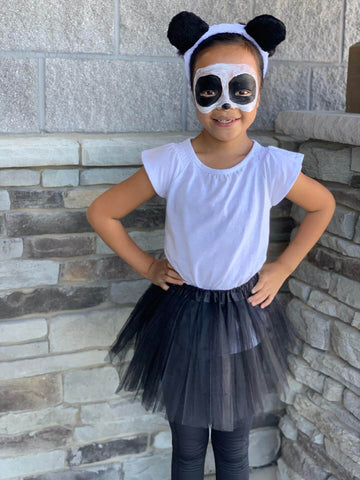 Girl wearing panda makeup and black and white tutu costume set.