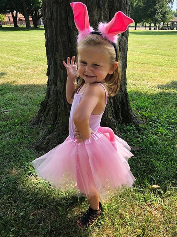 Little blonde girl posing & wearing bright pink tutu & ears set.