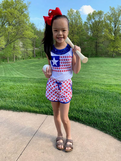 A young girl wears a 4th of July themed outfit and holds a baseball bat