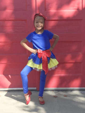 Little girl posing and wearing red, yellow & blue tutu with red headband.