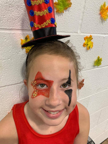 School age girl wearing small circus hat and red & black makeup.