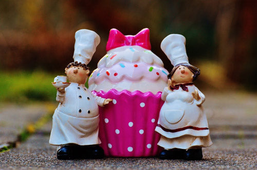 chef figurines next to a plastic cupcake