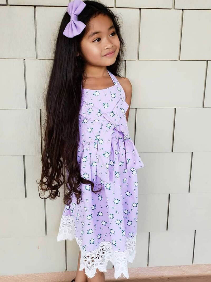 a little girl wearing a lavender Easter dress