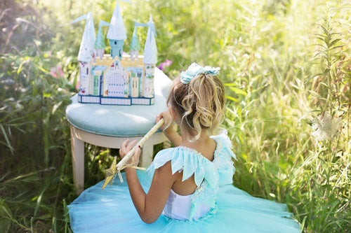 girl in a blue princess dress with castle