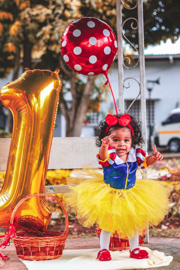 Baby girl with birthday balloons wearing red, blue and yellow tutu set.