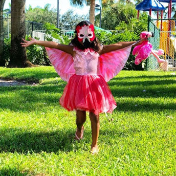 Little girl wearing pink wings, mask, and tutu outdoors.