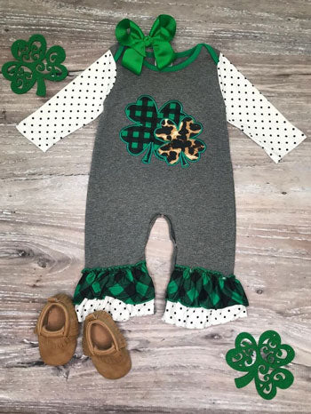 a baby romper with shamrocks and animal print