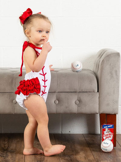 A young girl wears a white bodysuit with a baseball design
