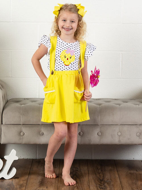 A little girl wears a yellow suspender outfit and yellow bows.
