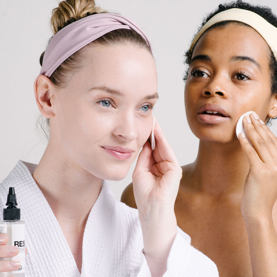Two women using cotton pads to apply RESET Organic Makeup Remover