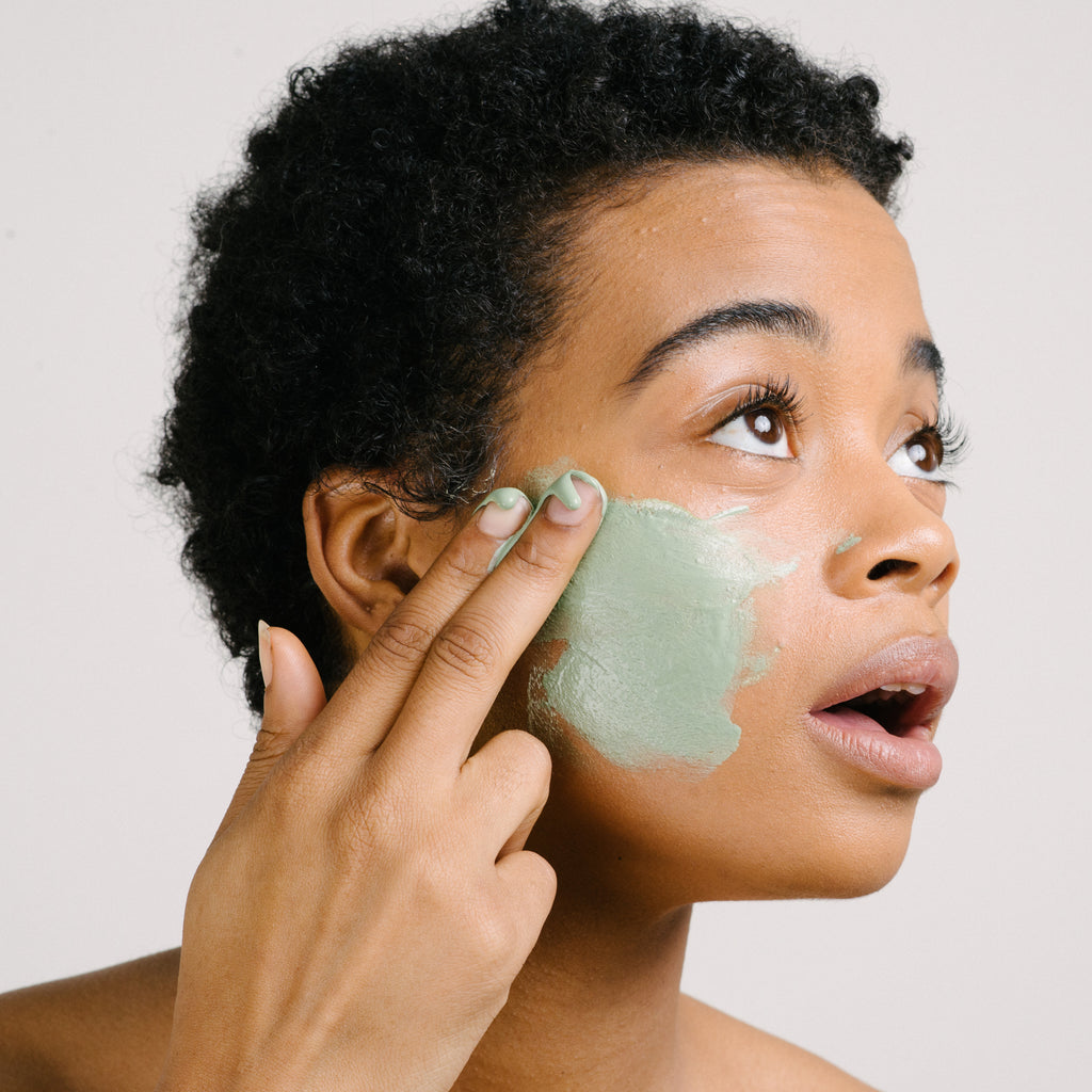 Woman rubbing a green face mask on her cheek