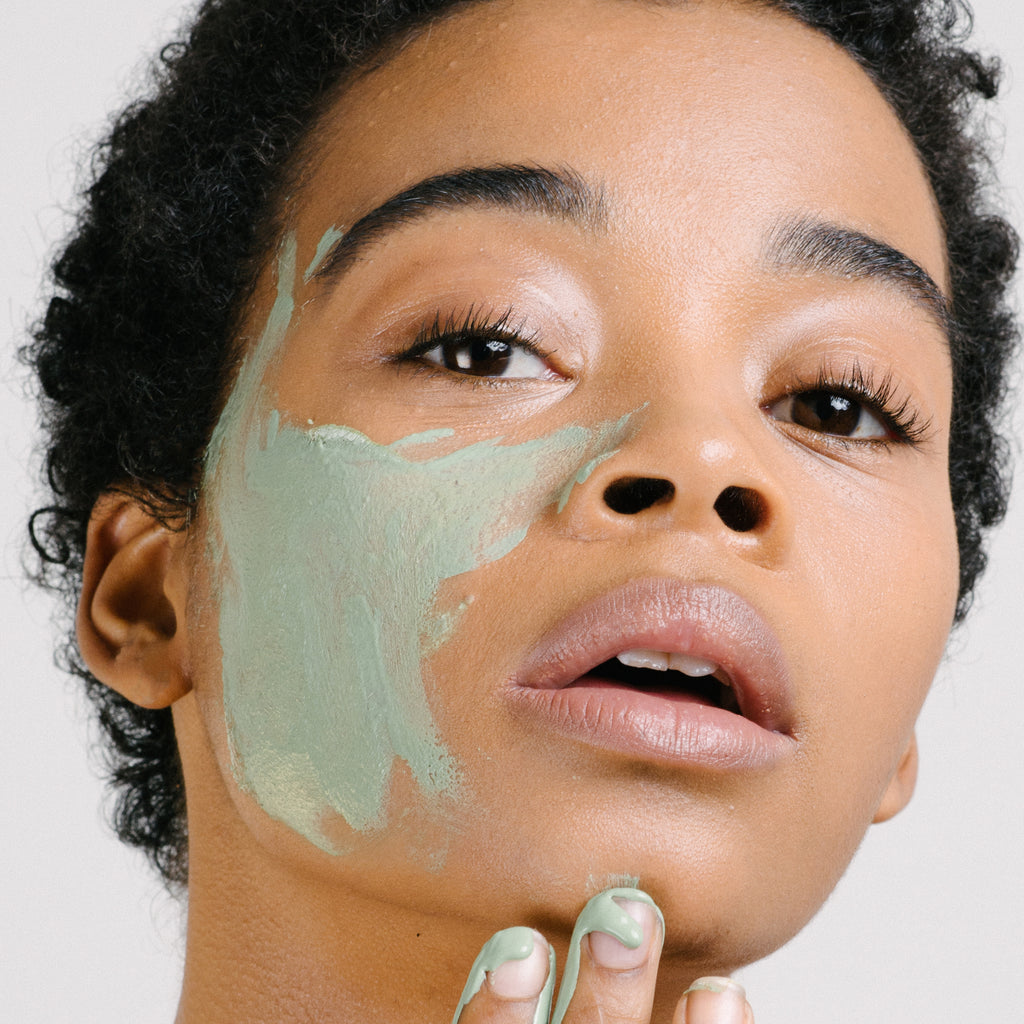 Woman with green face mask on her cheek