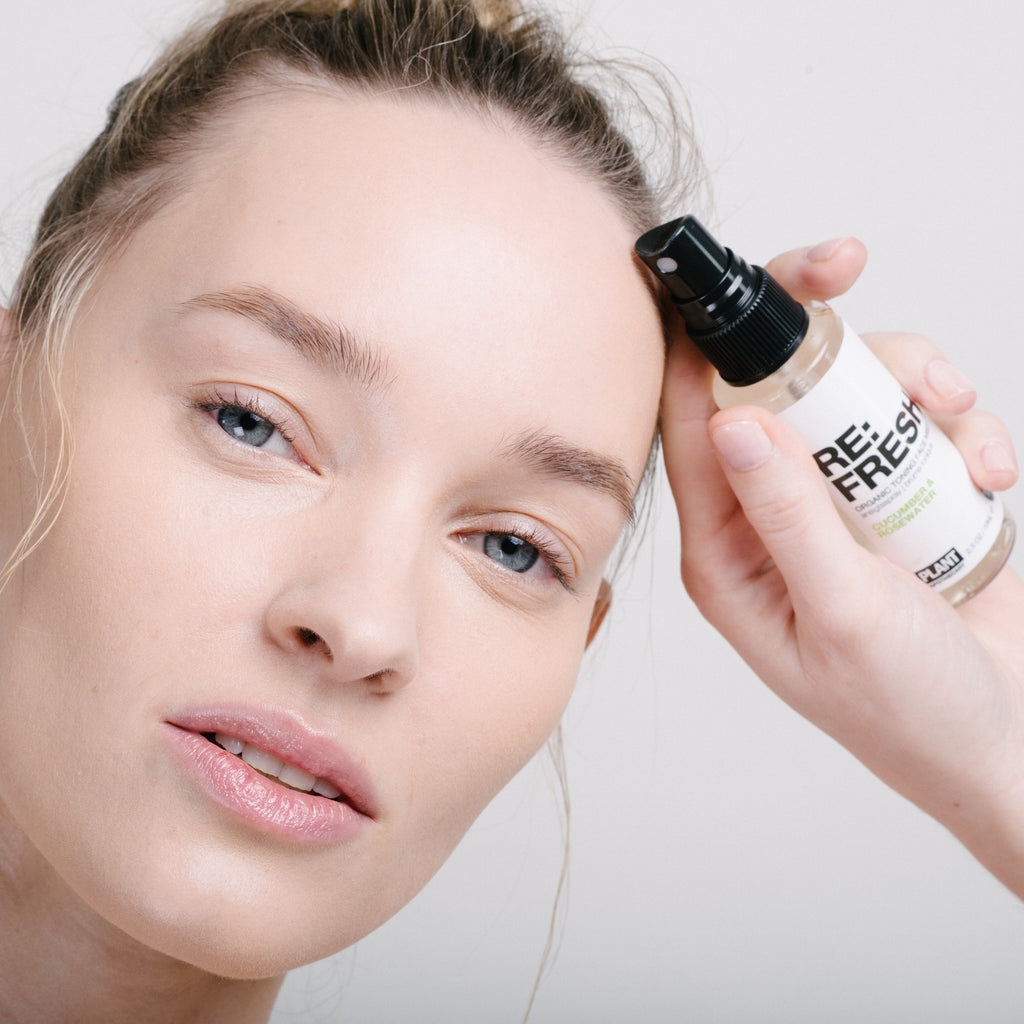 Woman holding RE: FRESH Organic Toning Facial Mist next to her forehead