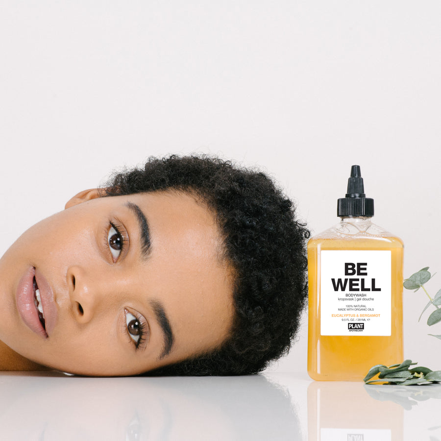 Woman laying her head next to BE WELL Organic Body Wash