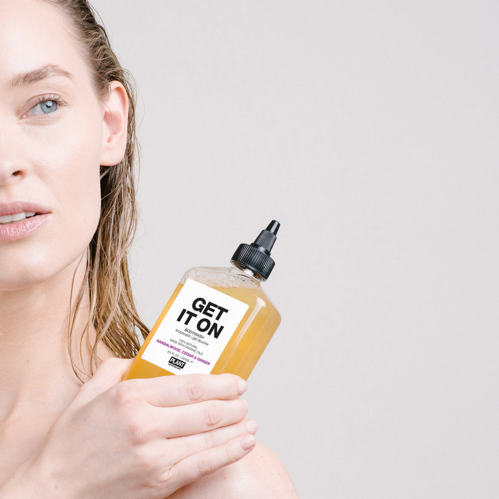 Woman holding GET IT ON Organic Body Wash next to her shoulder