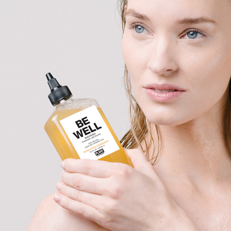 Woman holding BE WELL Organic Body Wash