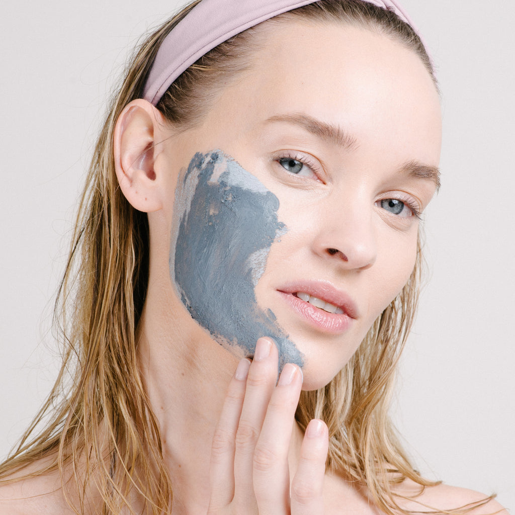 Woman applying NOT A SPOT Acne Treatment Mask to her cheek