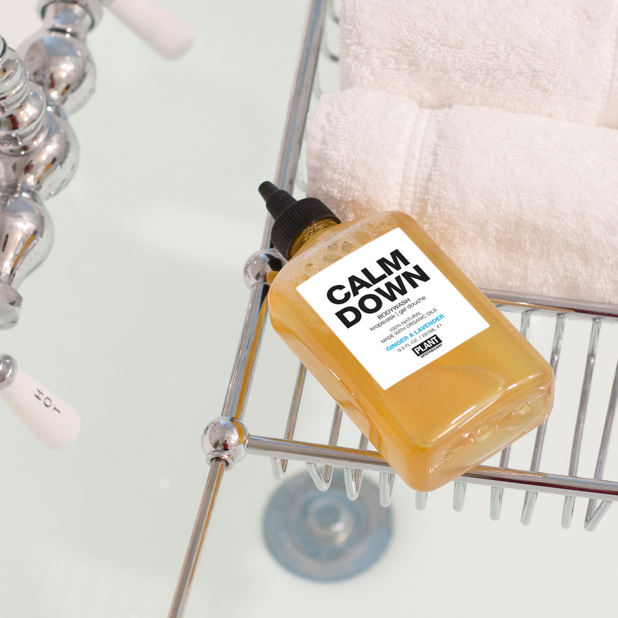 CALM DOWN Organic Body Wash laying on caddy tray in bathtub