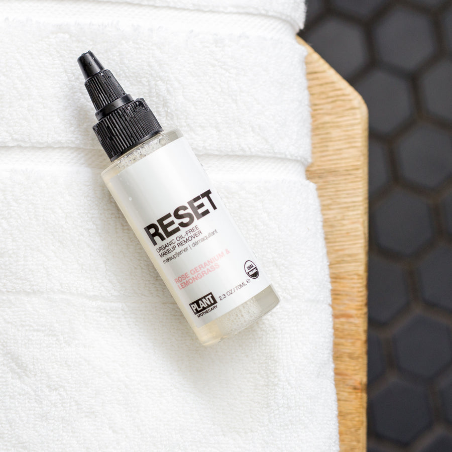 RESET Organic Makeup Remover bottle laying on white towel