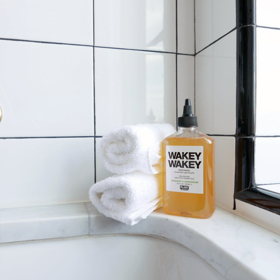 WAKEY WAKEY Organic Body Wash sitting next to two towels in a shower