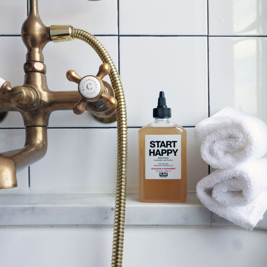 START HAPPY Organic Body Wash next to two white towels in a bathtub