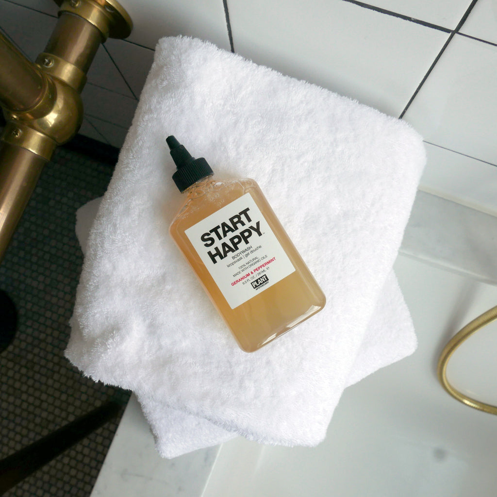 START HAPPY Organic Body Wash on a white towel