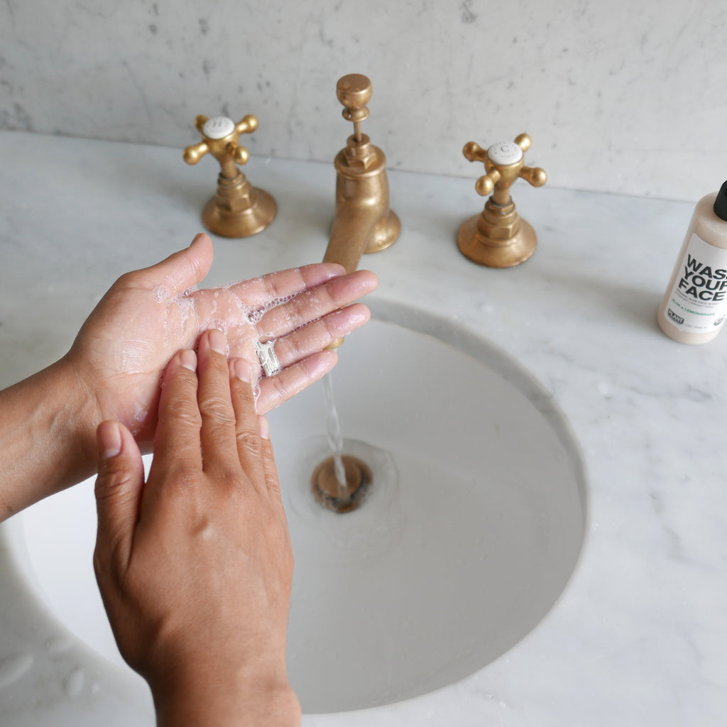 person rubbing cleanser on hands in sink