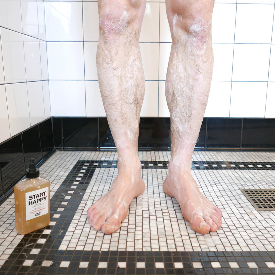 Man's legs in a shower with START HAPPY Organic Body Wash next to him