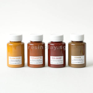 Four bottles of water-based acrylic pigments in a row. From the left, Yellow Oxide, Terracotta, Blue Red Oxide and Coade pigments are displayed.