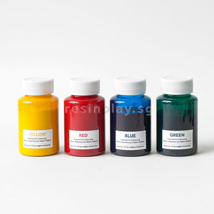 Four bottles of water-based acrylic pigments in a row. From the left, Yellow, Red, Blue and Green pigments are displayed.