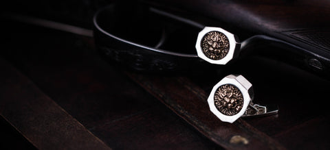 Trophy cufflinks with a lion motive and a hunting rifle in the background