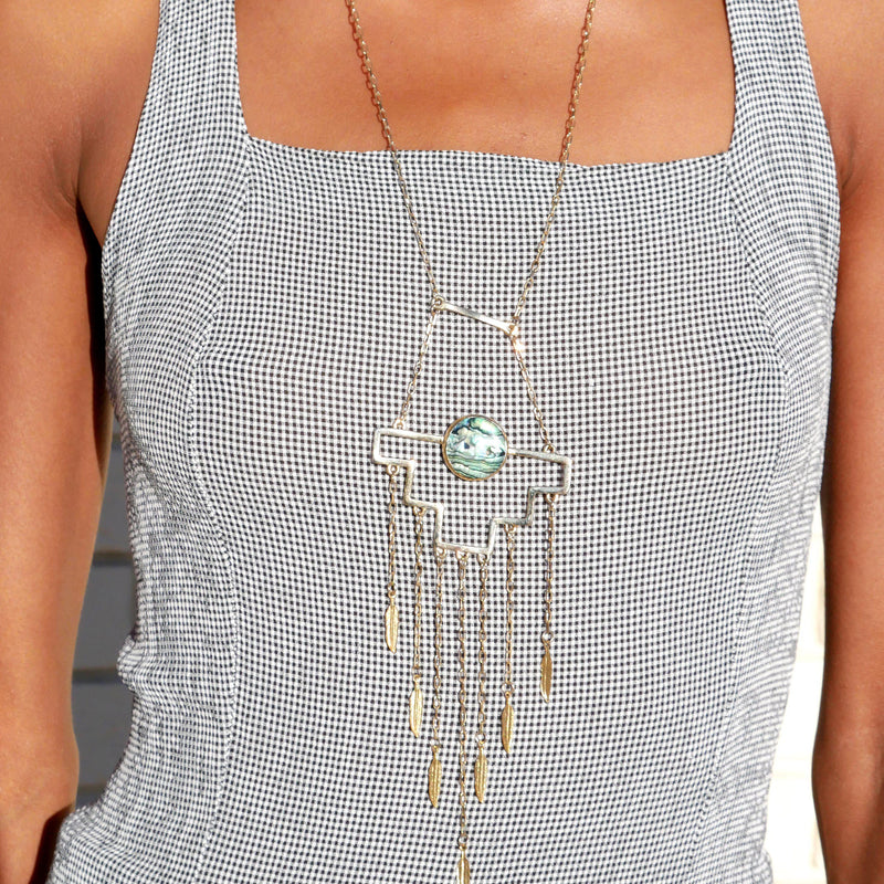 Chakana Necklace, necklace, Wherevershegoes, Jewelry, Necklaces, Abalone shell is held in a chakana cross design, and accompanied with playful, wavy chains and golden feather details on a long gold-plated chain necklace. Material: 24k gold-plated brass.Pendant Dimensions: 5cm L x 7.5cm WApprox Length: 48cm *perfectly positioned above the heart.Stones Origin: Baja California, Mexico.Due to the nature of the shell, expect minimal variations in it's colors and tonalities. by Quarzoma Jewelry