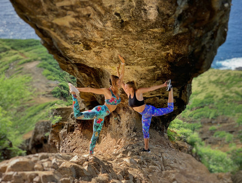 Two women doing dancer pose under a rock archway