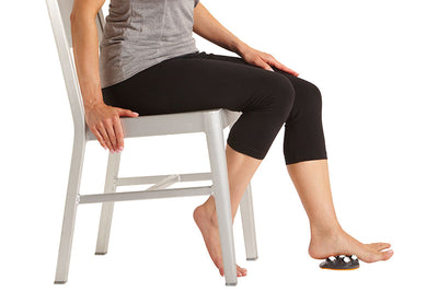 A person sitting in a chair while massaging bottom of feet using the Moji Pro Foot Massager