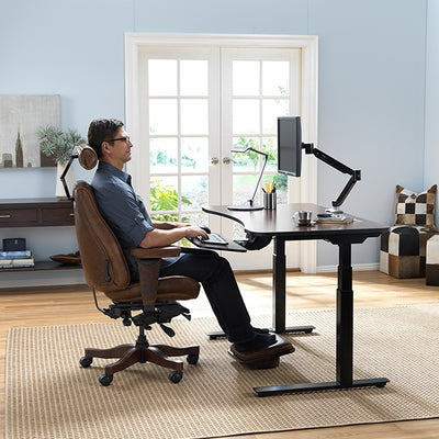 Man using the sitting feature of the AdaptDesk Standing Desk in his home office