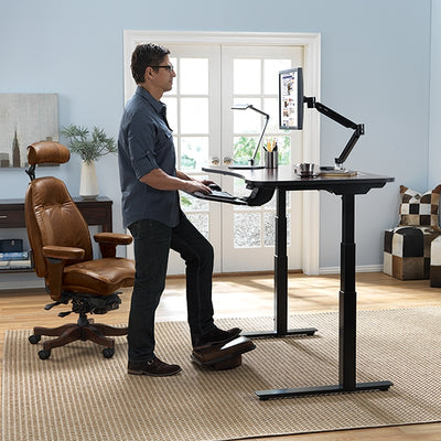 Man using the standing features of the AdaptDesk Standing Desk in his home office