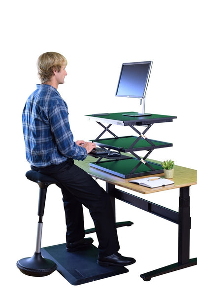 Man using the wobble stool at a work station