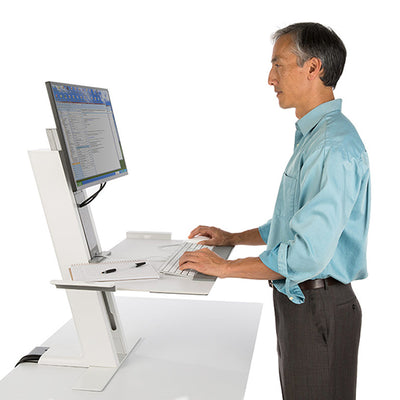Man standing and using the QuickStand Workstation