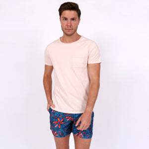 OWTS1804 Washed Coral pink garment dyed beach fit men's organic cotton t-shirt with chest pocket detail styles with OWSS1802 Jungle Floral Print swim short with elastic waist fabricated from recycled polyester