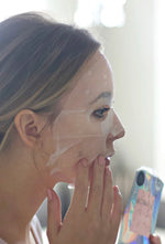 The Citrus Sheet Mask from sfglow applied on a female's face.