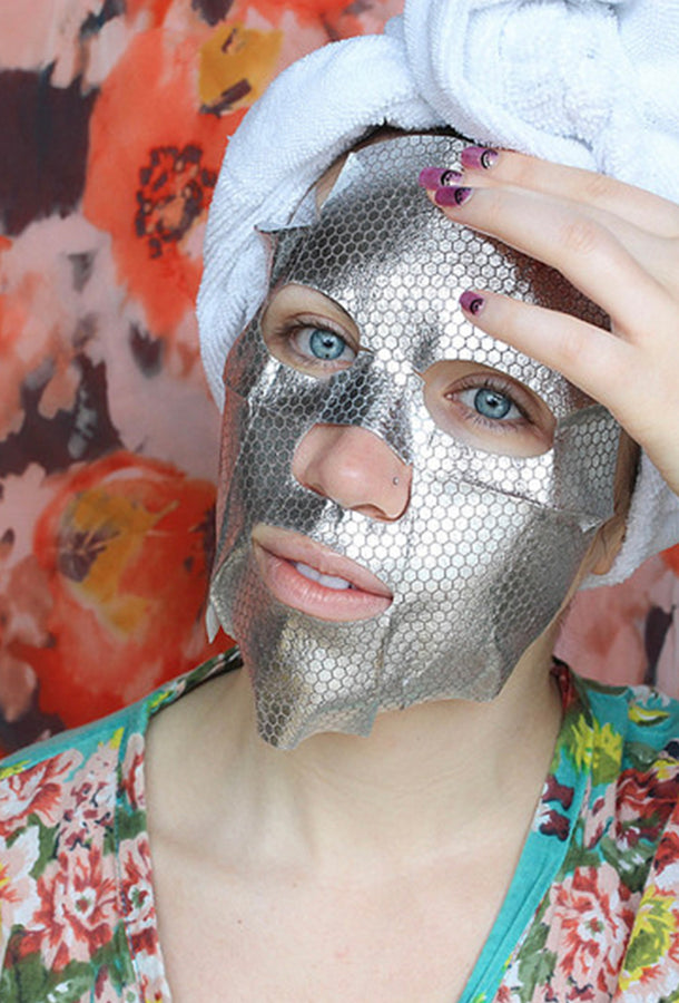 The Silver Mask Detox + Radiance Mask Sheet from sfglow applied on a face