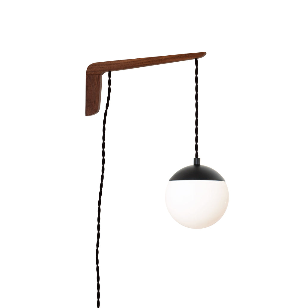 "Swing Arm Alto 6"". Shown with Walnut wood arm, Matte Black metal finish, and Black cord. (A15 light bulb shown, not included). Cedar and Moss."
