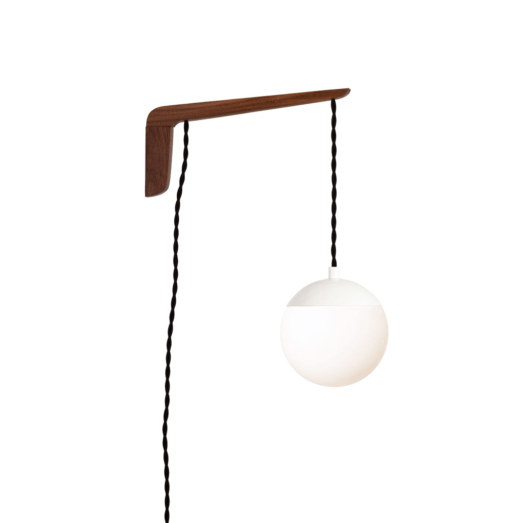 "Swing Arm Alto 6"". Shown with Walnut wood arm, White metal finish, and Black cord. (A15 light bulb shown, not included). Cedar and Moss."