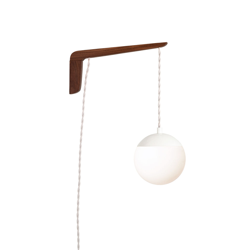 "Swing Arm Alto 6"". Shown with Walnut wood arm, White metal finish, and White cord. (A15 light bulb shown, not included). Cedar and Moss."