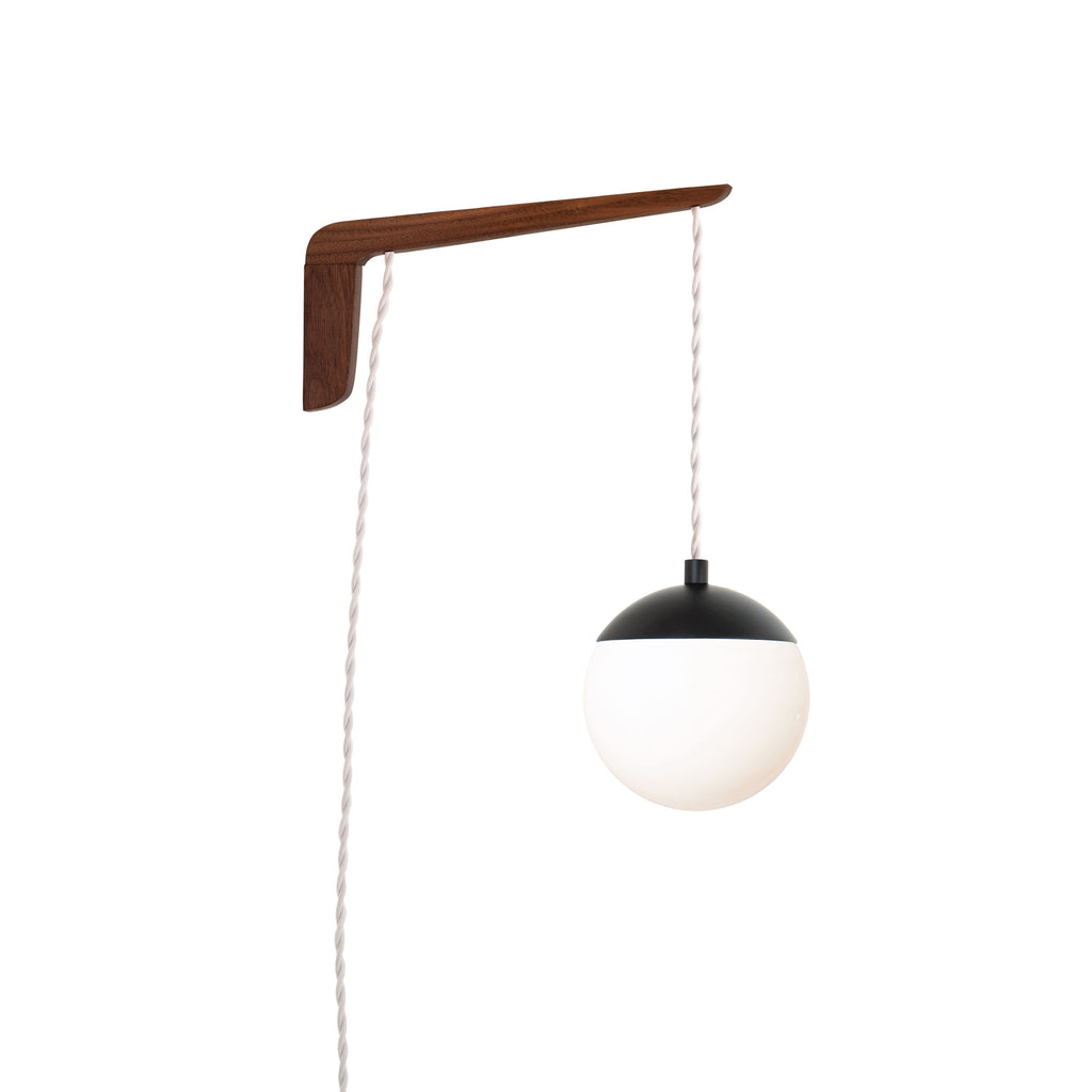 "Swing Arm Alto 6"". Shown with Walnut wood arm, Matte Black metal finish, and White cord. (A15 light bulb shown, not included). Cedar and Moss."