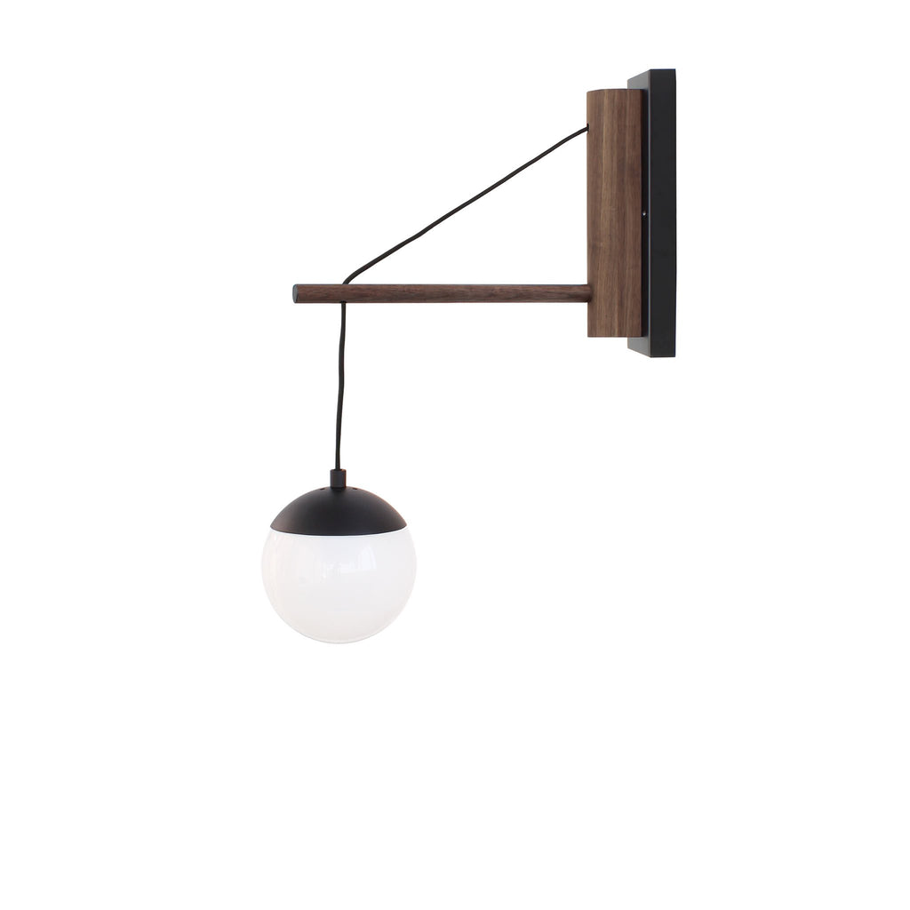 "Cedar and Moss. Alto 14"" Wood Arm Sconce, Hardwired. Shown in matte black finish with walnut wood and 6"" opal glass. (G16.5 bulbs shown, not included)."