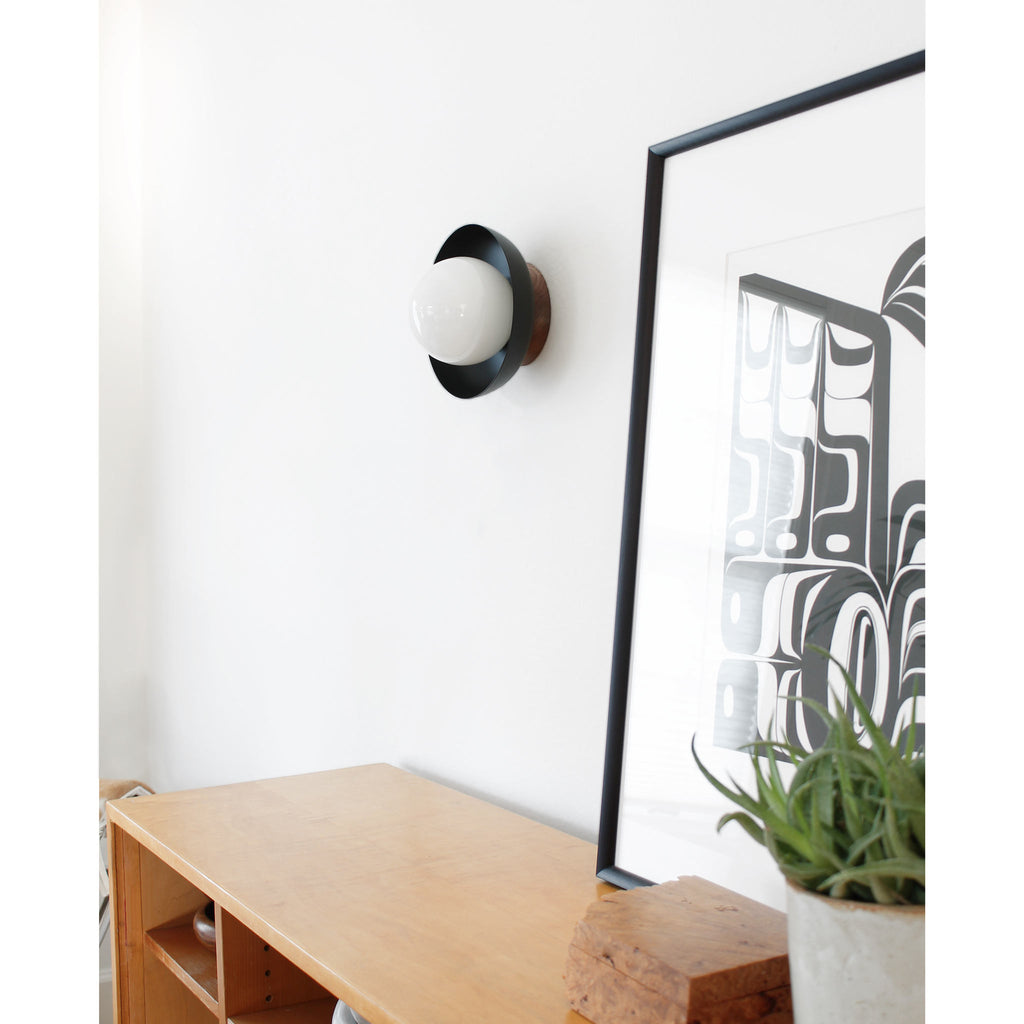 "Lexi Sconce. Shown in Matte Black finish with Walnut Wood canopy 5"" Opal globe. Light bulb included. Cedar and Moss."