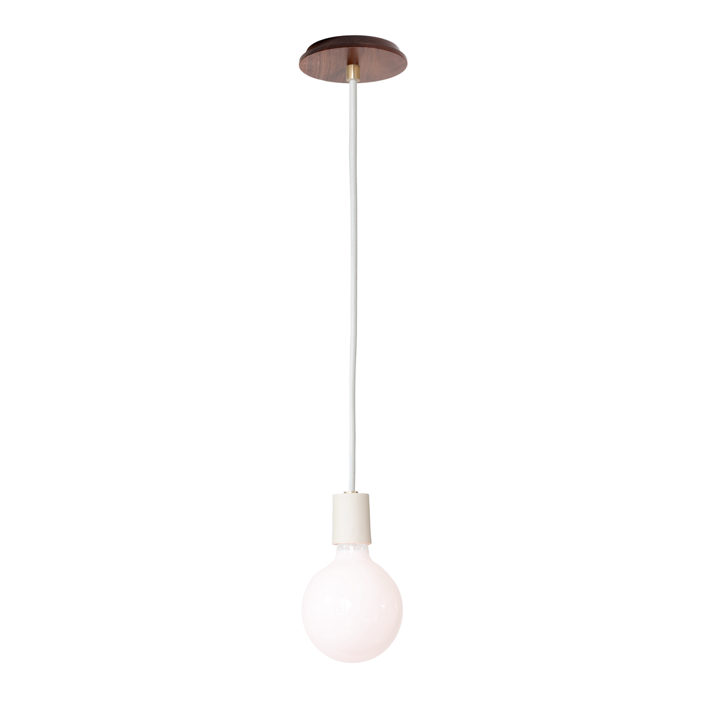 Swift Corded Pendant. Shown with Bone Ceramic Socket Cup, Walnut Wood Canopy, and White Round Cloth Cord. (G40 light bulb shown, not included). Cedar and Moss.