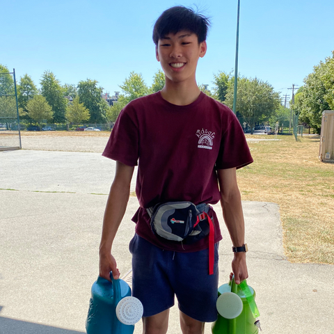Volunteer at KidSafe standing holding watering cans
