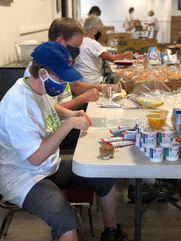 Volunteers packing healthy meals at Food for Thought
